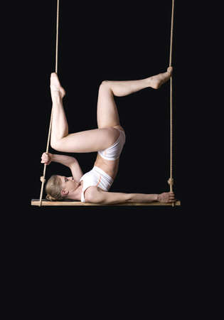 Young woman gymnast on a trapeze over black background  Stock Photo