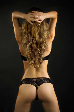 Sexy back of young beautiful blonde in lingerie over dark background  Stock Photo