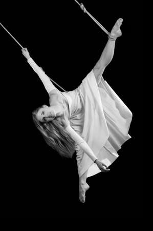 Young woman gymnast in white dress on rope on black background photo