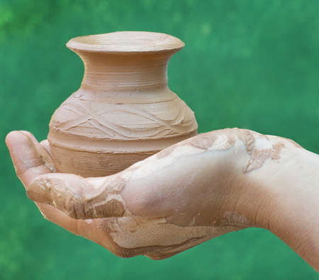 Close-up of hand holding pottery an  jar