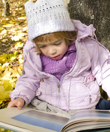 girl reads a book in an autumn park  Stock Photo - 15262102