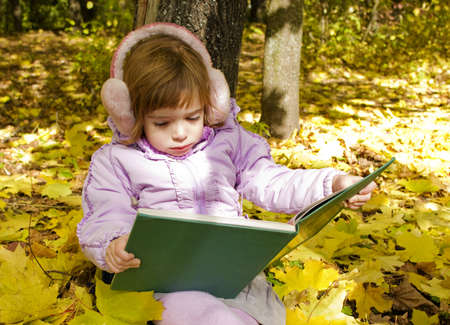 girl reads a book in an autumn park photo