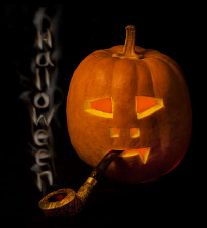 Halloween pumpkin  with smoke pipe and  lettering on black photo