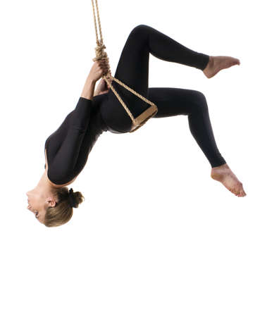 trapeze: Young woman gymnast on rope on white  background  Stock Photo