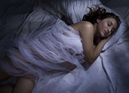moonlit: Young woman sleeping at night in bed