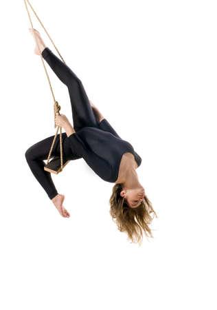 acrobacia: Mujer joven gimnasta sobre la cuerda en el fondo blanco Foto de archivo