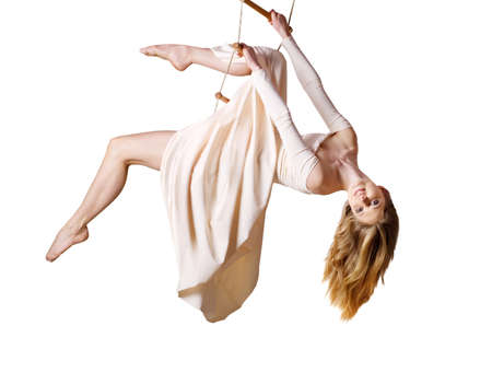 Young woman gymnast  on rope-ladder on white background