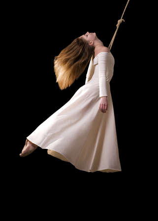 trapeze: Young woman gymnast in white dress on rope on black background