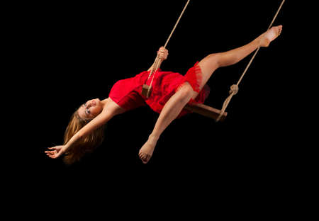performers: Young woman gymnast on rope on black background