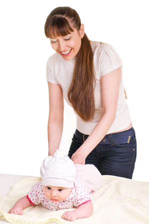 changing diaper: Mother changing babies cloth diaper over white background