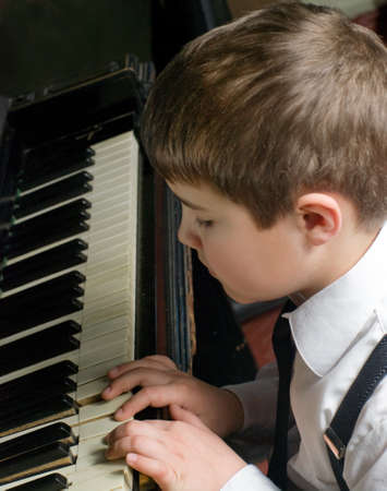 playing piano: little boy playing the piano Stock Photo