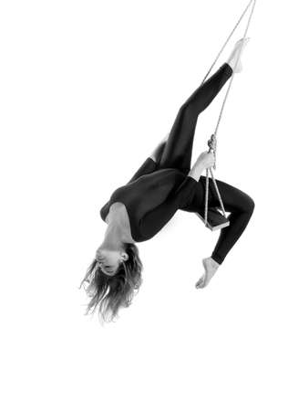 trapeze: Young woman gymnast on rope on white  background, black and white