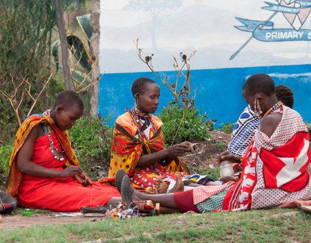 MAASAI MARA, KENYA-DECEMBER 27  Maasai women makes traditional necklace 27 December, 2012 at Maasai Mara, Kenya  The Maasai are the most famous tribe in Africa