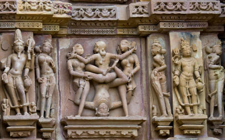 Stone carved erotic bas relief in Hindu temple in Khajuraho, India. Unesco World Heritage Site   photo