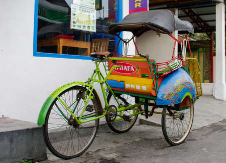 jogjakarta: JOGJAKARTA, INDONESIA- JAN 16: Becak are waiting for clients in the street on jan 16, 2011 in Jogjakarta, Indonesia. Riding a cycle rickshaw, a popular form of taxi here.