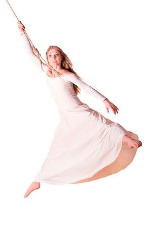 trapeze: Young woman gymnast in white dress on rope  White background  Stock Photo