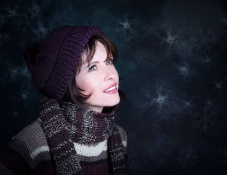 Smiling girl in winter style  on dark background; photo