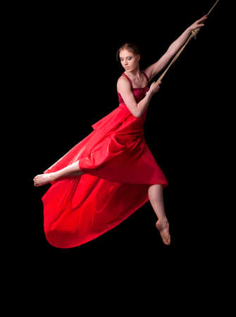Young woman gymnast in red dress on rope on black background  Stockfoto