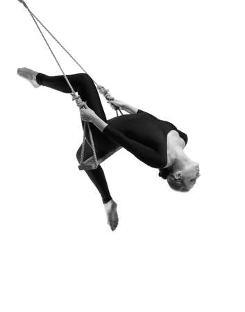 trapeze: Young woman gymnast on rope on white , Black and white Stock Photo