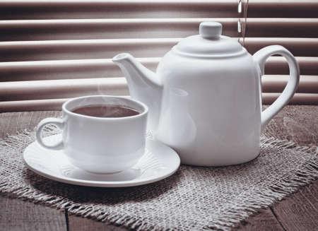 tazza di th�: tazza di t� con la teiera sul tavolo in legno vecchio sullo sfondo di tende