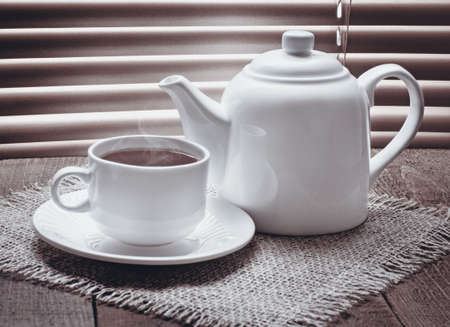tea cup with teapot on old wooden table against the background of blinds photo