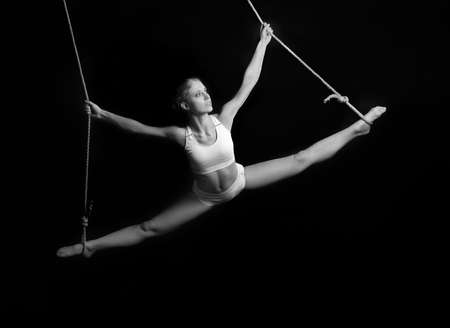 Young woman gymnast. On black background Stock Photo - 26211644