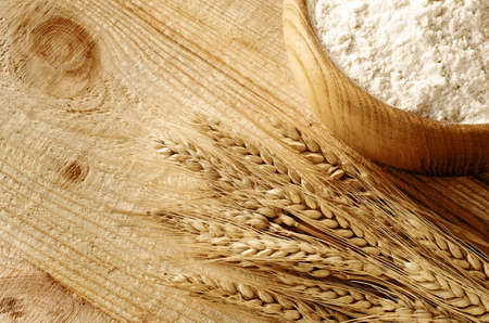 wheat isolated: Wooden bowl full flour and wheat ears on wooden background  Stock Photo