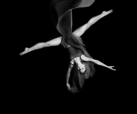 Young woman gymnaston rope on black background