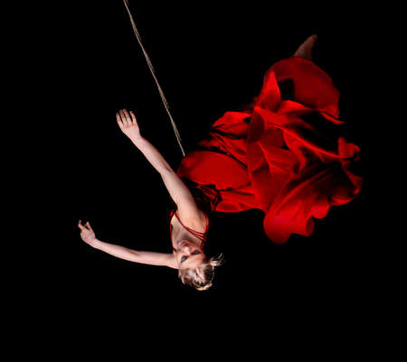 Young woman gymnast in red dress on rope on black background  Фото со стока