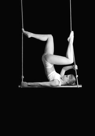 trapeze: Young woman gymnast on a trapeze over black background  Stock Photo