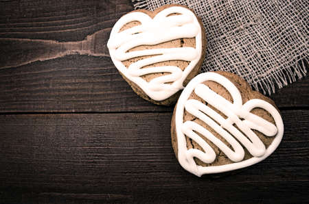 Homemade ginger cookies heart shaped over wooden table photo
