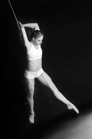 Young woman gymnast on black background Stock Photo