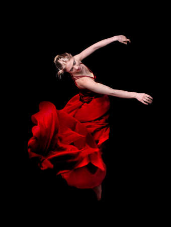 Young woman dancer in red dress  on black background photo