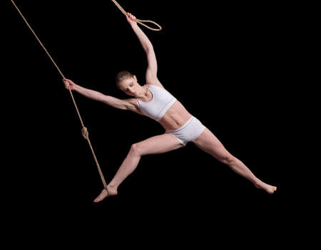 Young woman gymnast on rope on black background Stock Photo