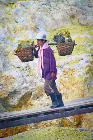 IJEN VOLCANO, INDONESIA - JAN 10:Worker carries sulfur inside crater on January 10, 2011 in Ijen Volcano, Indonesia. He carries the load of around 60kg to the top of the crater and then 3km down. Editorial