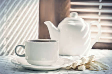 fireclay: tea cup with teapot  against the background of blinds Stock Photo