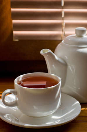 fireclay: tea cup with teapot on old wooden table against the background of blinds Stock Photo