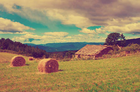 a house with a straw: Landscape with harvested bales of straw in field and stone house, Spain