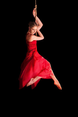 trapeze: Young woman gymnast in red dress on rope on black background