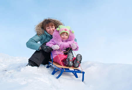 sledging: Mother and daughter sledging, nice winter scene