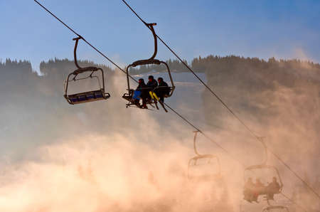 ukranian: BUKOVEL, UKRAINE - DEC 31, 2015: Skiers and snowboarders on a ski lift in Bukovel. Bukovel is the most popular  Ukranian mountain resort. Editorial