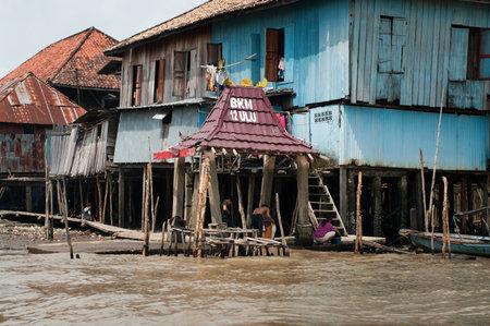 sumatra: PALEMBANG, INDONESIA - JULY 30, 2011: Wooden houses on piles on Musi River  in Palembang, Sumatra, Indonesia. Editorial