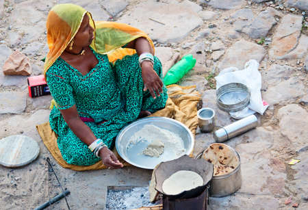 indigence: JAIPUR, INDIA - SEPT 26: An unidentified woman makes meal next the road on September 26, 2013 in Jaipur, Rajasthan, India.