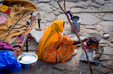 jaipur: JAIPUR, INDIA - SEPT 26: An unidentified woman makes meal next the road on September 26, 2013 in Jaipur, Rajasthan, India.
