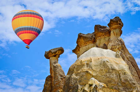 formations: Hot air balloon flying over spectacular landscape of fairy chimneys carved in volcanic tuff by erosion. Cappadocia, Turkey Stock Photo