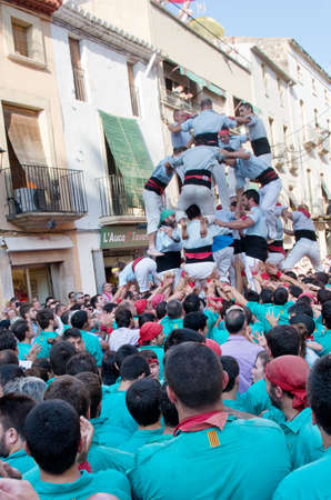 traditional climbing: TORREDEMBARRA, SPAIN - JULY 13, 2014: Castells Performance   in Torredembarra, Catalonia, Spain. A Castell is a  Human Tower  built traditionally in Catalonia.