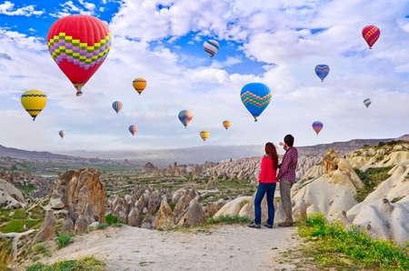 Couple of hikers enjoying valley view in Cappadocia, Turkey,