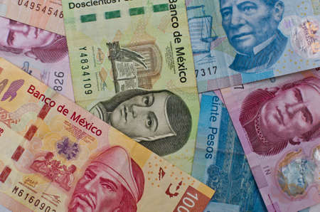 emerging markets: Different Mexican money bills stacked over each other forming a money background. Stock Photo