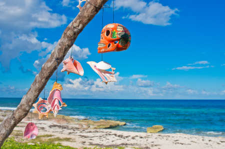 dry tree with different talismans on the Caribbean coast, Isla Mujeres, Mexico.