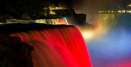 the edge of horseshoe falls: Niagara Falls lit at night show by colorful lights. American waterfall